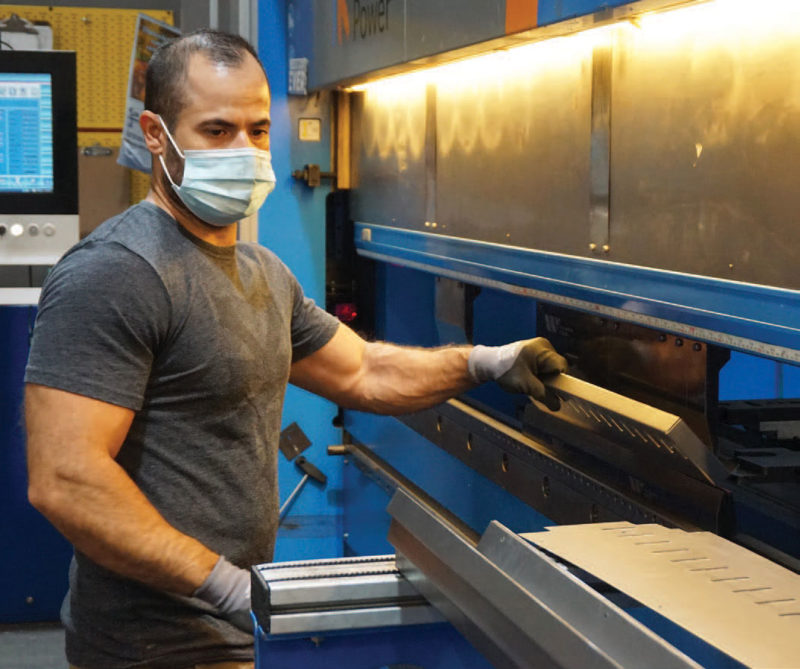 Jorge Santana working with machinery while wearing a mask