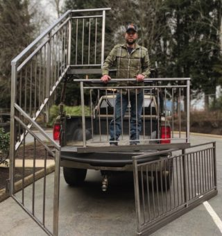 Clinton Child, owner/operator of Parkdale Metalworks, standing with a staircase rail he made for a home in the Gorge