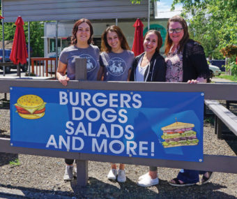 Four girls standing behind a sign, Burgers dogs salads and more!