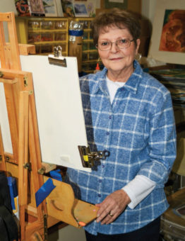 Sue Moore standing behind an easel