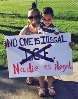 "Martha holding a sign with a young boy that says ""No one is Illegal. Nadie es ilegal"""