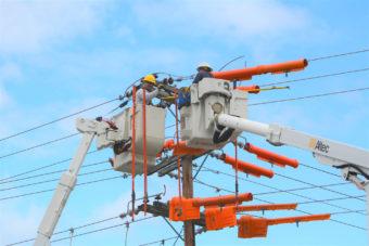 linemen in bucket truck working on power lines